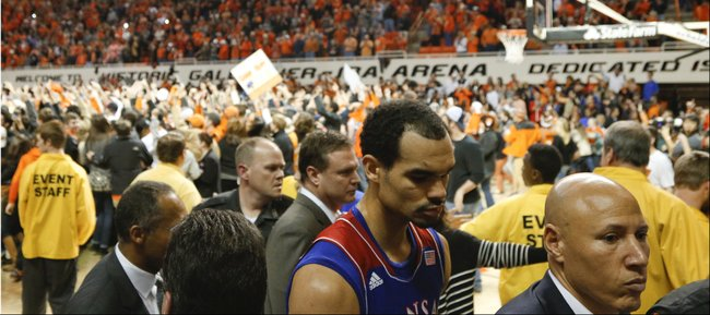 Kansas forward Perry Ellis makes his way to the locker room as Oklahoma State students storm the court following the Cowboys' 72-65 win on Saturday, March 1, 2014 at Gallagher-Iba Arena in Stillwater, Oklahoma.