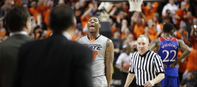Oklahoma State guard Marcus Smart celebrates before the Kansas bench as the Cowboys close out the game on Saturday, March 1, 2014 at Gallagher-Iba Arena in Stillwater, Oklahoma.