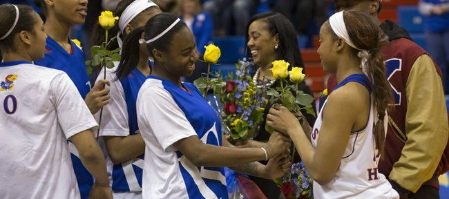 Kansas freshman Keyla Morgan, center, smiles as she hands senior teammate CeCe Harper a rose during senior night festivities, following their game against Iowa State, Saturday evening at Allen Fieldhouse.
