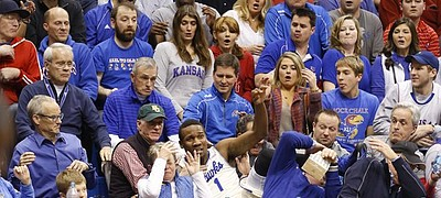 Fans react as Kansas guard Wayne Selden crashes into the seats after saving a ball that was tossed to teammate Joel Embiid for a bucket during the second half on Monday, Jan. 20, 2014, at Allen Fieldhouse.