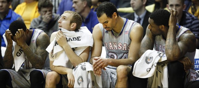 Kansas players Naadir Tharpe, left, Conner Frankamp, Perry Ellis and Tarik Black react to a foul called against the Jayhawks in the second half on Saturday, March 8, 2014 at WVU Coliseum in Morgantown, West Virginia.