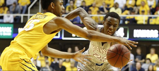 Kansas guard Andrew Wiggins and West Virginia guard Terry Henderson for a loose ball during the first half on Saturday, March 8, 2014 at WVU Coliseum in Morgantown, West Virginia.