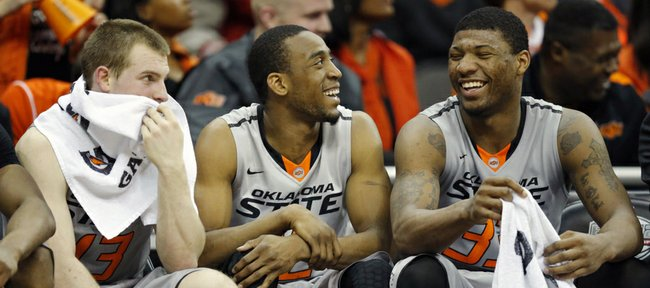Oklahoma State guards Phil Forte, III, left, Markel Brown, middle, and Marcus Smart, right, smile while on the bench late in the second half of their NCAA college basketball game against Texas Tech in the Big 12 men's tournament in Kansas City, Mo., Wednesday, March 12, 2014. Oklahoma State defeated Texas Tech 80-62.