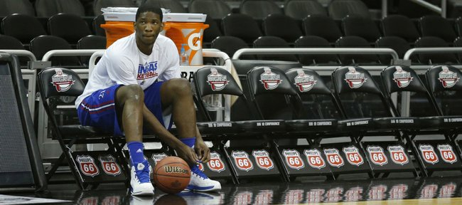 Kansas center Joel Embiid ties a shoe during practice for the Jayhawks' opening NCAA basketball game in the Big 12 men's tournament in Kansas City, Mo., Wednesday, March 12, 2014.