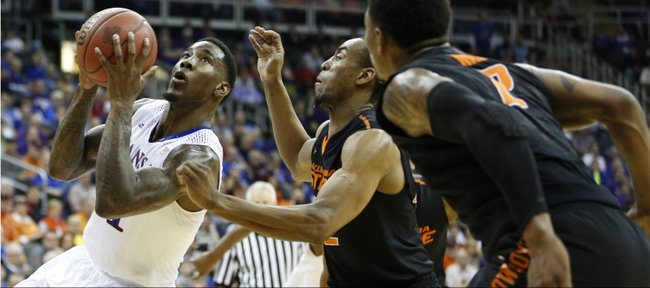 Kansas forward Jamari Traylor heads to the bucket against Oklahoma State defenders Markel Brown and Le'Bryan Nash, right, during the first half on Thursday, March 13, 2014 at Sprint Center in Kansas City, Missouri.