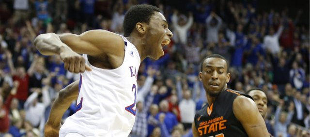 Kansas guard Andrew Wiggins celebrates after a lob dunk before Oklahoma State guard Markel Brown during the second half on Thursday, March 13, 2014 at Sprint Center in Kansas City, Missouri.