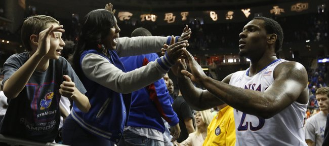 Kansas fans slap hands with forward Tarik Black and the rest of the team as they leave the court following the Jayhawks' 77-70 overtime win against Oklahoma State on Thursday, March 13, 2014 at Sprint Center in Kansas City, Missouri.
