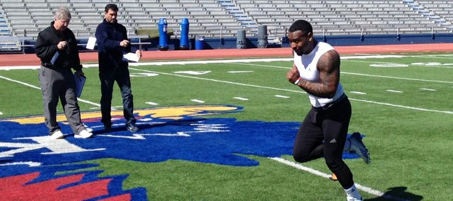 Former Kansas University running back James Sims sprints through the finish of the pro shuttle drill in front of a couple of NFL scouts on Friday at Memorial Stadium. Thirteen other former Jayhawks joined Sims at KU's annual Pro Day on Friday, March 14, 2014, at the KU football facilities.