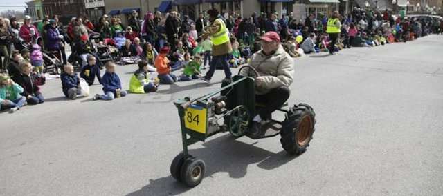 A man drives his small tractor down Massachusetts Street during Monday's St. Patrick's Day Parade.