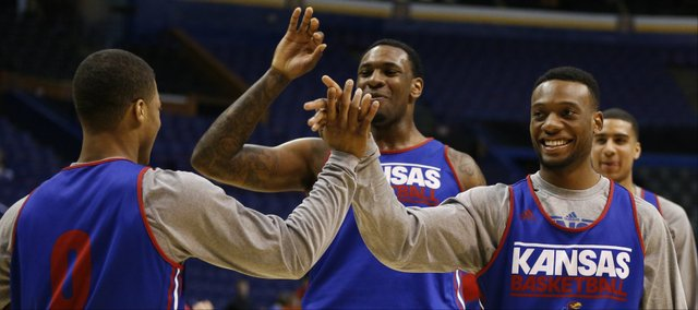 Kansas guard Naadir Tharpe, right, and forward Tarik Black slap hands with Frank Mason after Mason completed a dunk following a series of backflips during a day of press conferences and practices at the Scottrade Center in St. Louis on Thursday, March 20, 2014.