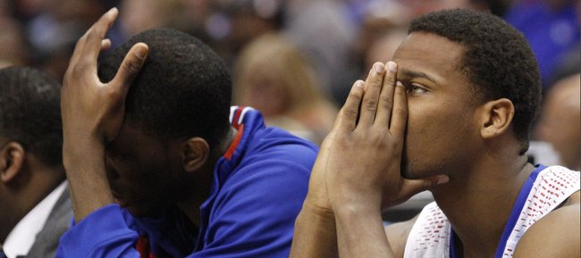 Kansas center Joel Embiid and Wayne Selden watch the closing seconds of the Jayhawks 60-57 loss to Stanford, Sunday March 23, 2014, at the Scottrade Center in St. Louis.