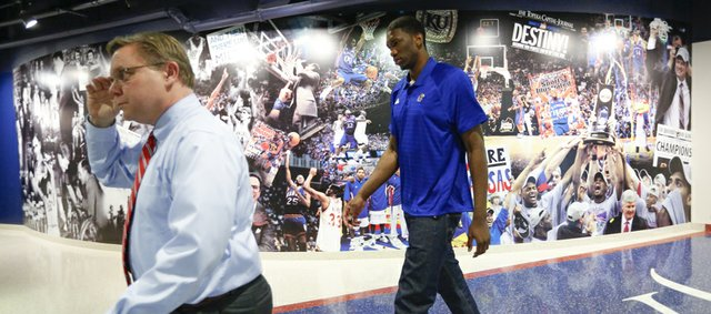 Kansas center Joel Embiid, right, walks past a collage in the northwest corner of Allen Fieldhouse behind assistant athletics director Chris Theisen following a news conference on Wednesday, April 9, 2014 at Allen Fieldhouse in which he announced his intention to enter the 2014 NBA Draft.