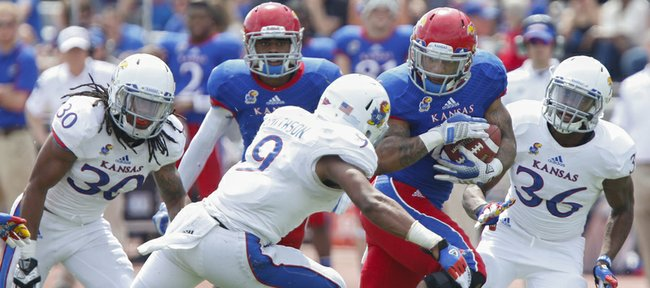 Blue Team running back Darrian Miller cuts through White Team defenders Fish Smithson (9), Tevin Shaw (30) and Chevrick Graham (36) during the second half of the Kansas Spring Game on Saturday, April 12, 2014 at Memorial Stadium. Nick Krug/Journal-World Photo