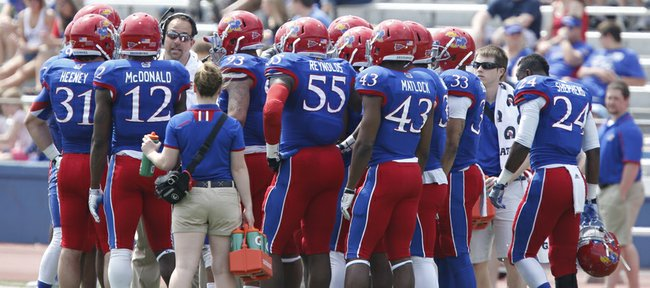 Blue Team coach John Reagan directs his players in the huddle during a break in the first half of the Kansas Spring Game on Saturday, April 12, 2014 at Memorial Stadium. Nick Krug/Journal-World Photo