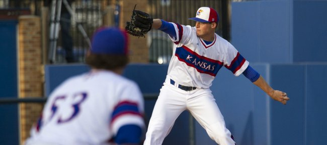 Kansas junior pitcher Wes Benjamin delivers a pitch as junior Blair Beck holds a runner near first base during Kansas' game against Oklahoma, Friday evening at Hoglund Ballpark.