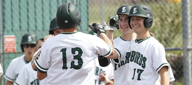 Free State senior Zach Bickling (13) gets high-fives from teammates after clearing the bases with a home run against Bishop Miege on Friday, April 25, 2014, at FSHS.