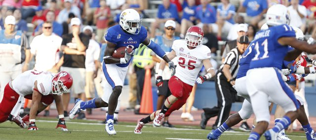 Kansas receiver Josh Ford takes off up the field after a reception against South Dakota during the first quarter on Saturday, Sept. 7, 2013 at Memorial Stadium.