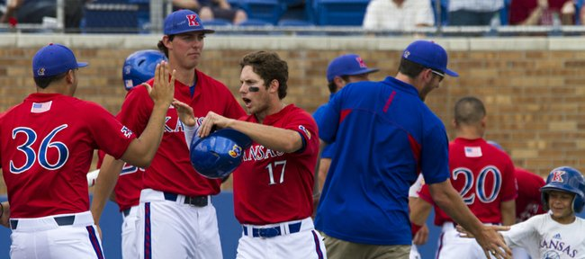 Kansas junior Michael Suiter (17) is met by teammates in front of the dugout after scoring a run during Kansas' game against West Virgina, Sunday afternoon at Hoglund Ballpark. The Jayhawks swept the three game series by holding off the Mountaineers, 9-8, in the final game.