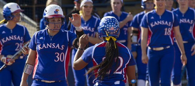 Kansas freshman Harli Ridling (30) slaps hands with senior Ashley Newman (22) following Newman's run during their game against Texas Tech, Friday at Arrocha Ballpark.