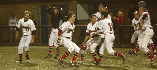 Members of the Lawrence High baseball team clear out of the dugout after winning the City Showdown against Free State, 5-4 in nine innings, on Thursday at Hoglund Ballpark.