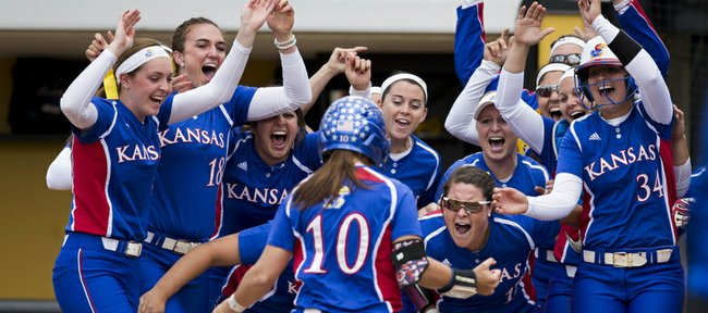 Members of the Kansas University softball team celebrate at the plate after Taylor Hatfield (10) hit a two-run home run in the first inning of Friday's NCAA regional softball game against Nebraska on Friday, May 16, 2014, in Columbia, Mo.