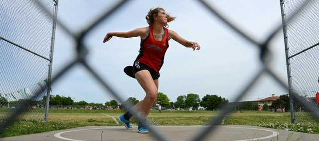 Lawrence High's Matia Finley throws the discus Friday during regional track and field action at Shawnee Mission South.
