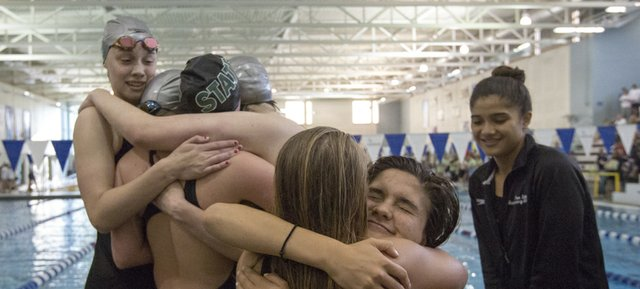Members of the Free State swim team share hugs near the pool following the final event at the state swimming and diving championships, held Saturday in Topeka.