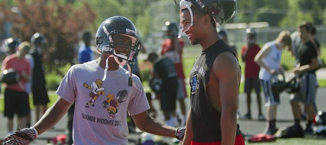 Lawrence High's Ivan Hollins, left, and J'Moni Bryant participate in the Lions' summer football camp on Monday, June 2, 2014. Hollins and Bryant were part of a large group of LHS sophomores who played plenty as sophomores and will be counted on to help lead the team during their junior season.