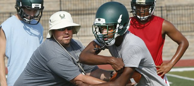 Free State senior running back Joe Lane takes a handoff from assistant coach Mike Gillman during the second day of the Firebirds' football camp on Tuesday, June 3, 2014, at FSHS.