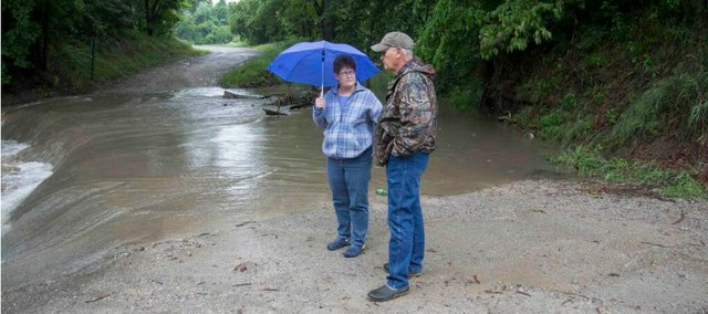As 3 inches of rain fell in the Lawrence area Monday into Tuesday some small creeks overflowed, like this one at East 1075 and 1000 roads. Local residents Casey and Jenie Van Gemerem, who live at 1073 N. 1172 Road, came out to see the water just down from their house.