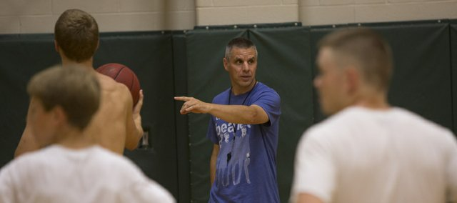 Free State High boys basketball coach Chuck Law, center, instructs campers Wednesday at FSHS.