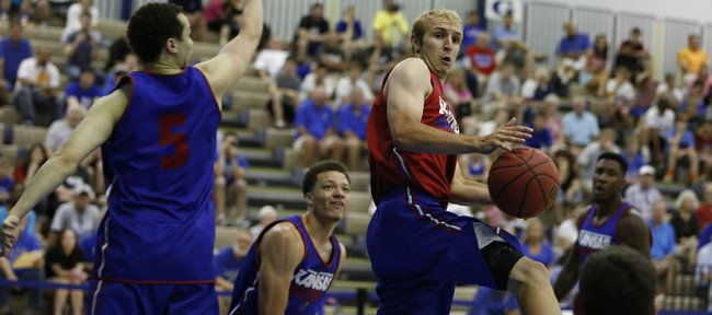 Red Team guard Conner Frankamp dishes a pass under the bucket and past Blue Team player Evan Manning (5) and Brannen Greene during a scrimmage on Wednesday, June 11, 2014 at the Horejsi Center.