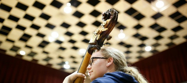Gabrielle McCurdy, of Liberty, Mo. stands behind her bass as she listens to an instructor during a jazz improvisation class at the Midwestern Music Camp on Tuesday at Murphy Hall on the campus of Kansas University.