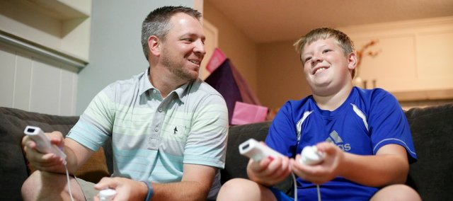 Brandon Urban and his 13-year-old son, Ben, joke with each other while playing a game of FIFA soccer on Nintendo Wii at their Lawrence home on a recent day. Ben was recently diagnosed with Klinefelter's syndrome, a rare disease that gives males an extra X chromosome. Brandon has been participating in charity events to raise money and awareness about the disorder.