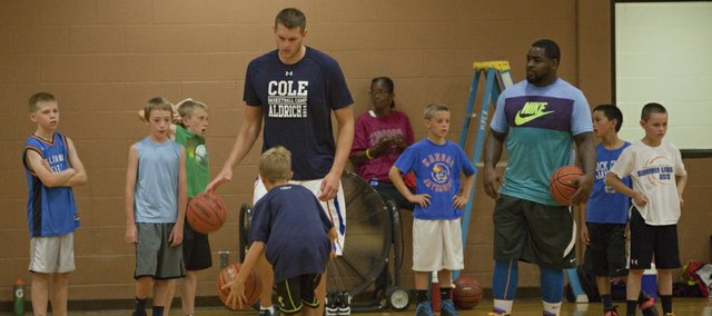 Former Kansas basketball player and current NBA player Cole Aldrich, left, and former KU player Sherron Collins work with campers at Aldrich's basketball camp Monday, July 7, 2014, at Robinson Gym at KU.