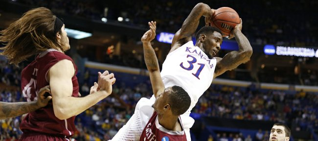Kansas forward Jamari Traylor grabs an offensive rebound over Eastern Kentucky guard Orlando Williams during the second half on Friday, March 21, 2014 at Scottrade Center in St. Louis.