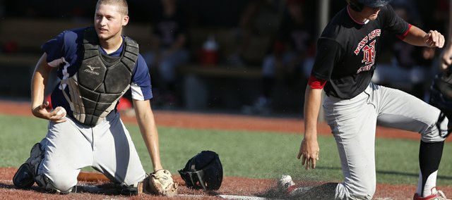 Raiders catcher Bowen Cunningham pulls the ball from his glove after Next Level Baseball runner Dawsom Pomeroy stands up after scoring during the fourth inning on Tuesday, July 8, 2014 at Lawrence High School.