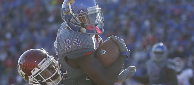 Kansas cornerback JaCorey Shepherd is pulled down by Oklahoma receiver Sterling Shepard following his interception of OU quarterback Blake Bell during the third quarter on Saturday, Oct. 19, 2013 at Memorial Stadium.