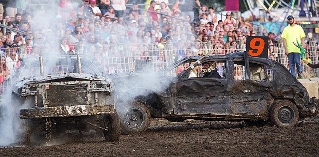 Anti-freeze drains from Clint Doherty's Crown Victoria as it is engulfed in smoke while Dougas Gipson (9) and his 1999 Lincoln finish off the competition to win the full-size class round of the demolition derby, held Friday evening at the Douglas County Fairgrounds.