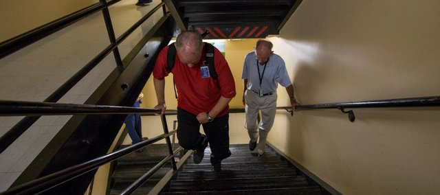 "Rick McNabb, of Lawrence, left, climbs stairs at Lawrence Memorial Hospital on Friday while ""coach"" Jerry Waugh provides support and friendship. Four years ago, McNabb suffered an aneurysm that led to a stroke that left him paralyzed and without sensation on the left side of his body. McNabb is attempting to climb the equivalent of Mount Everest while raising money for charity."