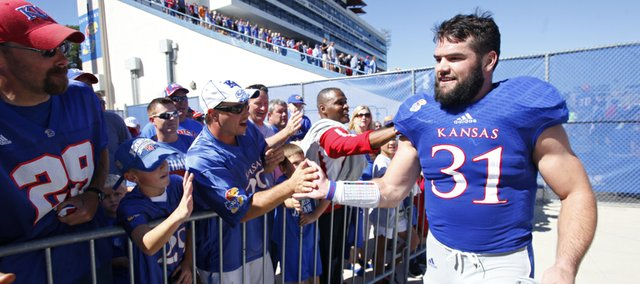 Kansas linebacker Ben Heeney celebrates with fans after the Jayhawks' 13-10 win over Louisiana Tech on a walk-off fieldgoal from kicker Matthew Wyman, Saturday, Sept. 21, 2013 at Memorial Stadium.