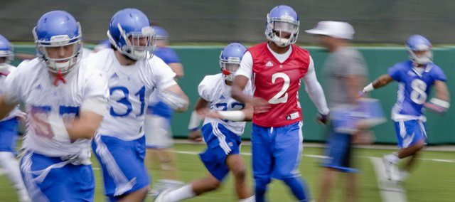 Kansas University quarterback Montell Cozart (2) runs side sprints with teammates during the Jayhawks' first practice of the season, Friday, Aug. 8, 2014, on the fields outside Memorial Stadium.  Also pictured are, from left, linebackers Jake Love (57) and Ben Heeney (31), safety Cassius Sendish (33) and wide receiver Nick Harwell (8).