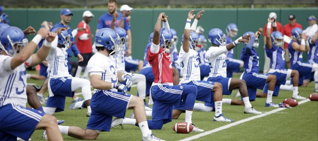 KU quarterback Montell Cozart, center in red, and the rest of the Jayhawk team warm up during the first KU football practice Friday on the football practice fields south of Memorial Stadium.