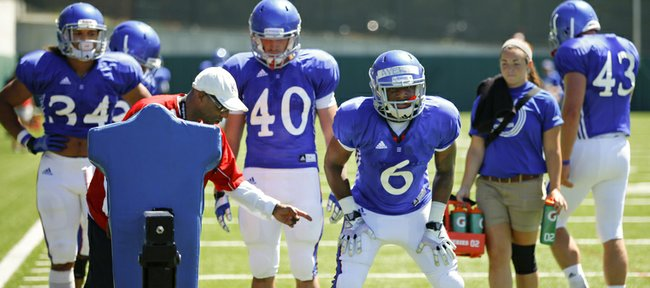 Kansas' Corey Avery (6) takes some instruction from running backs coach Reggie Mitchell during practice on Tuesday, Aug. 12, 2014.