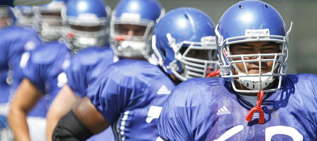 Kansas University Ngalu Fusimalohi, (63) participates in drills during a team practice Thursday, August 14, 2014.