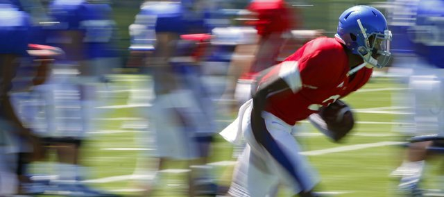 Kansas quarterback Montell Cozart bursts off the line during running drills on Tuesday, Aug. 12, 2014.