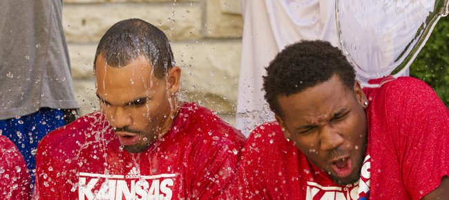 Kansas men's basketball players Perry Ellis, left, and Wayne Selden react as head coach Bill Self helps pour buckets of ice water onto them while they participate in the ALS Ice Bucket Challenge, Sunday afternoon outside of the Wagnon Student Athlete Center.