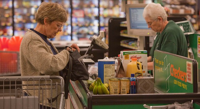 Delores Kaczor, of Lawrence, left, buys groceries Wednesday at Checkers, 2300 Louisiana, as cashier Betty Grems, tallies the total. Kansans pay more sales tax on groceries than everyone in the country except residents of Mississippi.