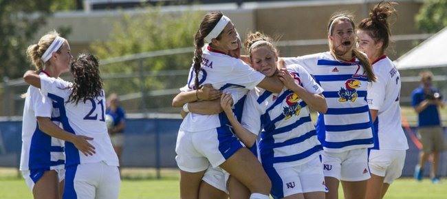 Kansas senior forward Ali Kimura (12) is all smiles as she celebrates a her goal with teammates that broke a 0-0 first half tie during their game against Wake Forest at the Jayhawk Soccer Complex on Sunday afternoon.