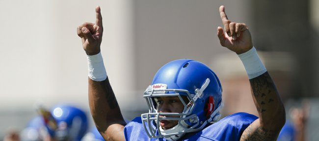Kansas receiver Nick Harwell raises his arms as he and his teammates stretch out during practice on Tuesday, Aug. 12, 2014.